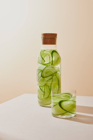 Photo for Glass and bottle with cork filled with fresh water and sliced cucumbers on beige background - Royalty Free Image
