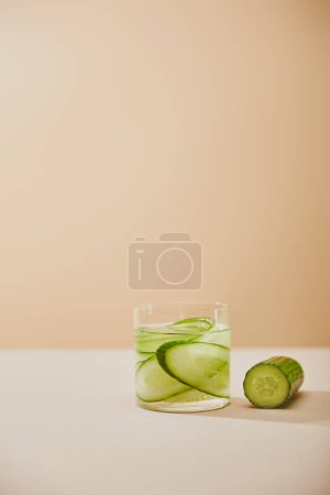 Glass of water with sliced cucumbers on table isolated on beige