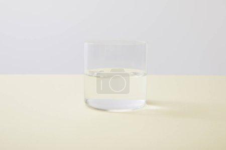 Photo pour Verre avec de l'eau sur surface jaune isolé sur gris - image libre de droit