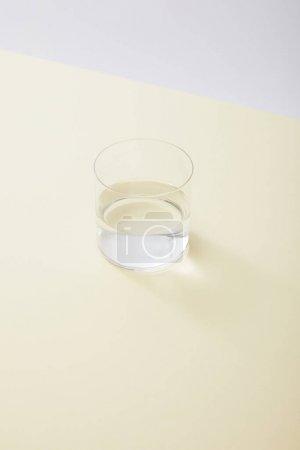 Photo pour Vue grand angle du verre avec de l'eau sur la surface jaune isolé sur gris - image libre de droit