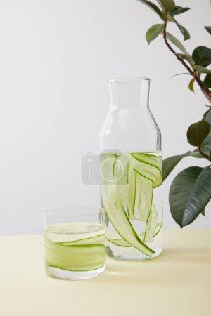 Photo pour Bouteille et verre avec eau et concombres tranchés et feuilles de plantes isolées sur gris - image libre de droit