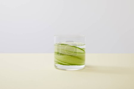 Photo for Glass with fresh water and sliced cucumbers on yellow surface isolated on grey - Royalty Free Image