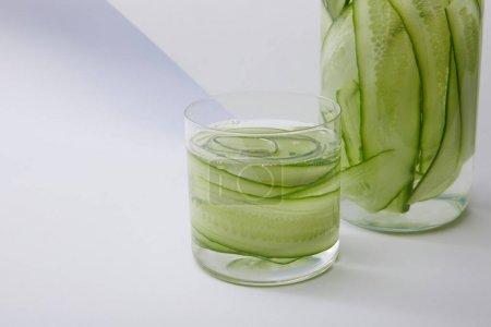 Photo pour Vue rapprochée de la bouteille et du verre avec boisson fraîche et concombres tranchés sur fond gris et blanc - image libre de droit