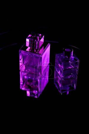 Purple perfume bottles on mirror dark surface isolated on black