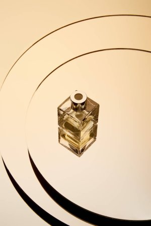 High angle view of golden perfume bottle on round mirror surface with reflection