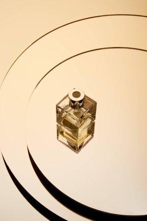 Photo pour Vue grand angle du flacon de parfum doré sur une surface miroir ronde avec réflexion - image libre de droit