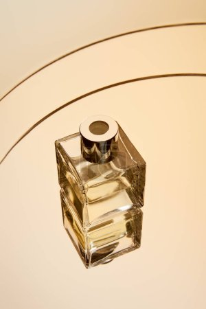 Photo for High angle view of perfume bottle on round beige mirror surface with reflection - Royalty Free Image