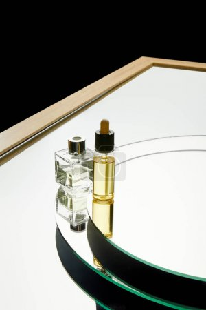 Photo for High angle view of aromatic perfume bottle and serum bottle on mirror surface isolated on black - Royalty Free Image