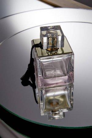 Photo pour Flacon de parfum violet sur miroir rond gris réfléchissant - image libre de droit