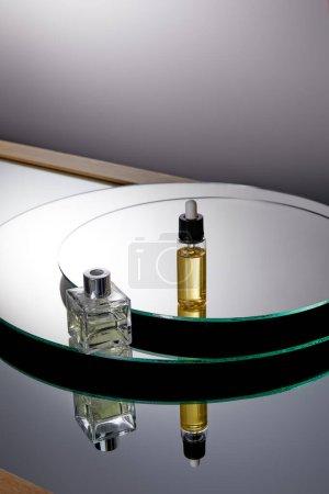 Photo pour Vue grand angle du flacon de parfum et du flacon de sérum sur la surface du miroir - image libre de droit