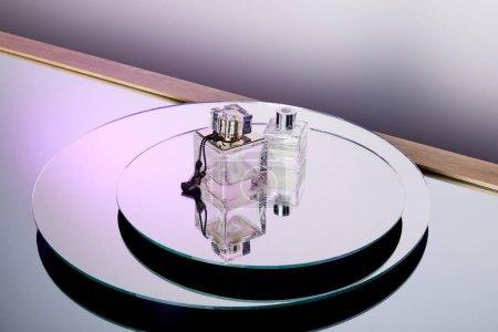Photo pour Vue grand angle des bouteilles de parfum violet de luxe sur la surface du miroir rond - image libre de droit