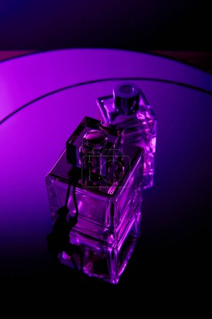 Photo for Top view of perfume bottles on dark dramatic violet round mirror surface - Royalty Free Image