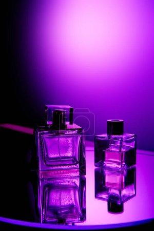 Photo pour Flacons de parfum violet sur la surface du miroir rond et tache lumineuse sur le fond - image libre de droit