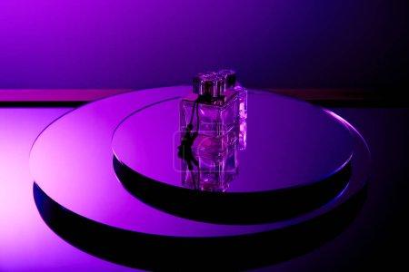 Foto de Frascos de perfume de lujo violeta en superficie redonda espejo con reflejo aislado en púrpura - Imagen libre de derechos