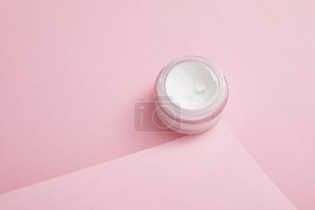 Cosmetic cream in glass jar on pink background