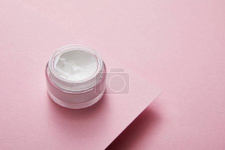 Photo pour Vue grand angle de la crème cosmétique en pot de verre sur fond de papier rose - image libre de droit