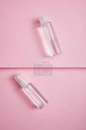 Photo pour Vue du haut d'un vaporisateur et d'un flacon de lotion transparents avec liquide sur fond rose - image libre de droit