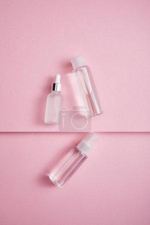 Photo pour Vue du dessus du flacon cosmétique transparent, du vaporisateur et du flacon de sérum avec liquide sur fond de papier rose - image libre de droit