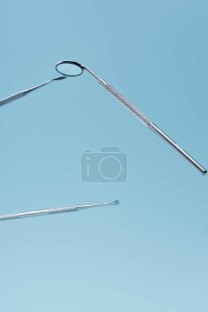 Metal dental professional instruments levitating isolated on blue background