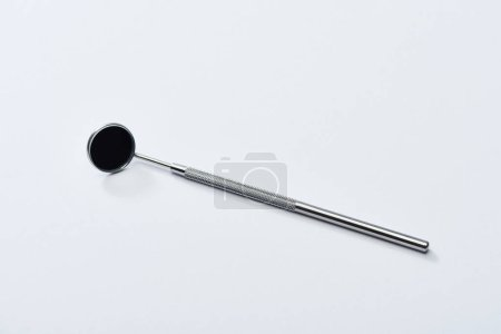 High angle view of stainless dental mirror for teeth examination on grey background