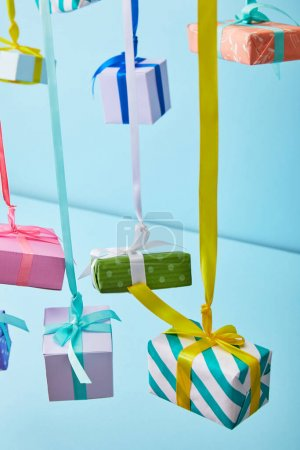 Photo for Festive colorful gift boxes hanging on ribbons on blue background - Royalty Free Image