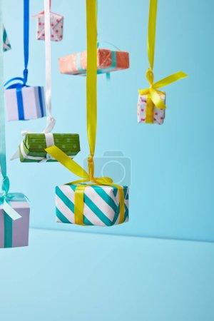 Photo pour Boîtes cadeaux colorées festives suspendues sur des rubans sur fond bleu - image libre de droit
