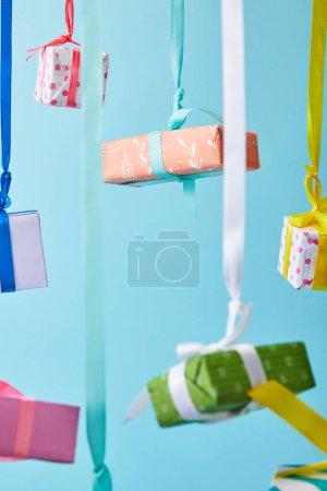 Photo pour Foyer sélectif de boîtes-cadeaux colorées festives suspendues sur des rubans isolés sur bleu - image libre de droit