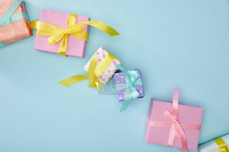 Photo for Top view of festive colorful gift boxes on blue background - Royalty Free Image