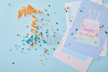 Photo pour Vue du haut des confettis colorés près des cartes de vœux d'anniversaire sur fond bleu - image libre de droit