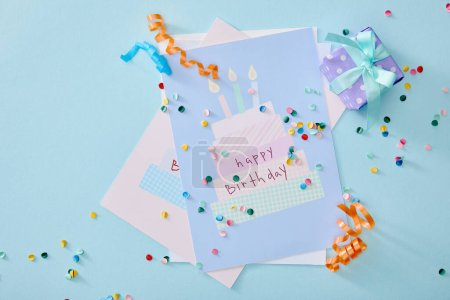 Photo for Top view of colorful confetti near birthday greeting cards on blue background - Royalty Free Image