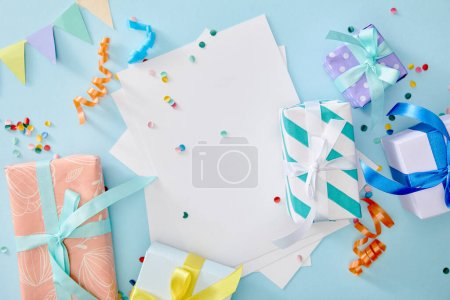 Photo for Top view of colorful confetti near blank paper and gift boxes on blue background - Royalty Free Image