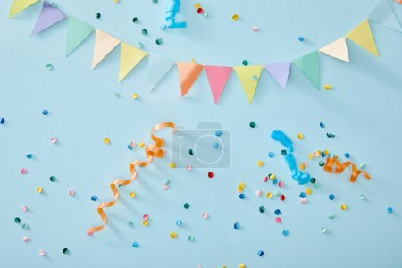 top view of colorful confetti on blue background