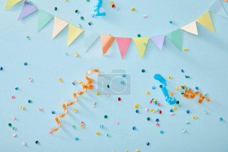 Photo pour Vue de dessus des confettis colorés sur fond bleu - image libre de droit