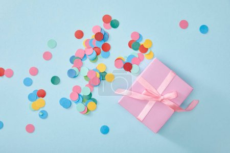 Photo for Top view of colorful confetti near pink present on blue background - Royalty Free Image