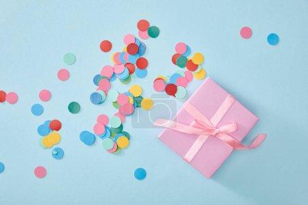 Photo pour Vue de dessus de confettis colorés près de rose présents sur fond bleu - image libre de droit