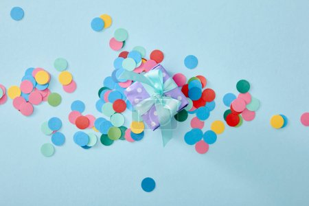top view of colorful confetti near present on blue background