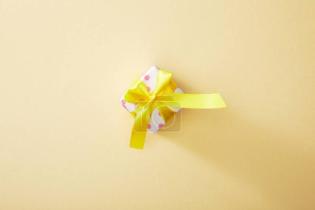 top view of festive colorful gift box on beige background