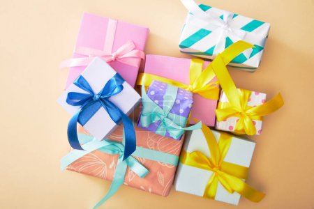 Photo for Top view of festive colorful gift boxes on beige background - Royalty Free Image