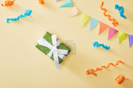 Photo for Top view of festive colorful confetti and gift on beige background - Royalty Free Image