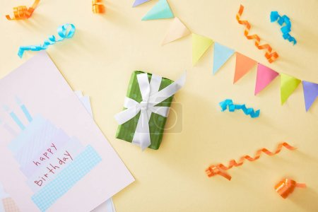 Photo for Top view of festive colorful confetti and gift with happy birthday greeting card on beige background - Royalty Free Image