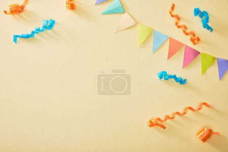 Photo for Top view of festive colorful confetti on beige background - Royalty Free Image
