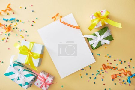 Photo for Top view of festive colorful confetti and presents near blank paper on beige background - Royalty Free Image