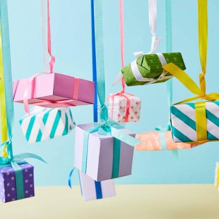 Photo pour Boîtes-cadeaux colorées accrochées au ruban sur fond bleu - image libre de droit