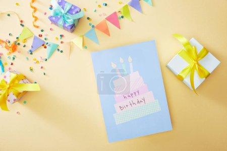 Foto de Vistas superiores de confeti � n y cajas de regalo alegres y coloridas cerca de la tarjeta de felicitación de cumpleaños feliz en segundo plano beige. - Imagen libre de derechos