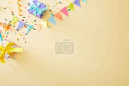 Foto de Vista superior de confeti colorido festivo y cajas de regalo sobre fondo beige - Imagen libre de derechos