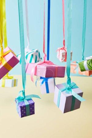 Photo pour Boîtes cadeaux colorées festives suspendues sur des rubans sur fond bleu et jaune - image libre de droit