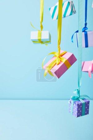 Foto de Cajas de regalo de colores festivos colgando de cintas sobre fondo azul - Imagen libre de derechos