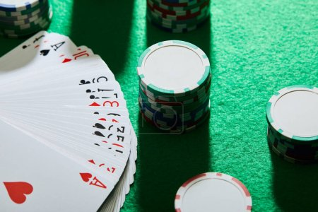 Photo for High angle view of playing cards with casino chips on green background - Royalty Free Image