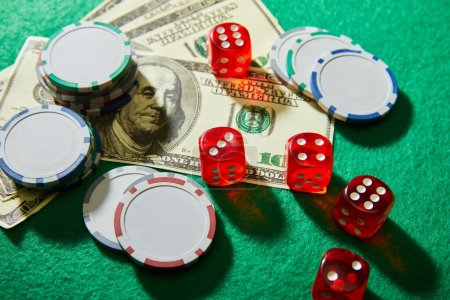 Photo for High angle view of dollar banknotes, dice and casino chips on green - Royalty Free Image