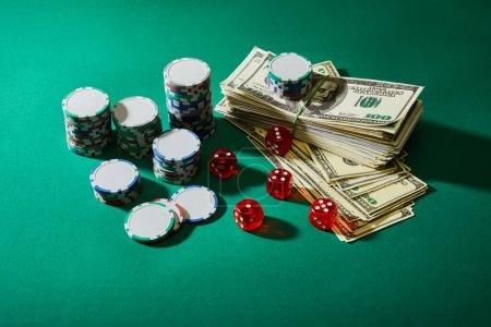 Photo pour Vue à angle élevé des billets en dollars, des dés et des jetons de casino sur vert - image libre de droit
